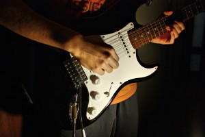 Hands playing an electric guitar.  Fame and fortune bring happiness – right?