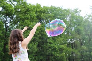 Female child using a large bubble wand to form a big soap bubble in the air. Half term: heaven or hell?