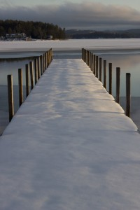 Snow-covered jetty onto a still lake. Conceal, or reveal?