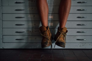 Pare of bare male legs hanging over a set of filing drawers, weating unlaced boots.  Are you a master of procrastination?