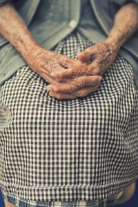 Elderly woman's hands folded in her lap.  Time: too much, too little, to late?