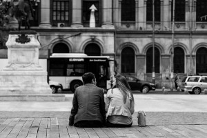 Couple sitting close together in a city square.  Navigating by dating: strengthening our relationships