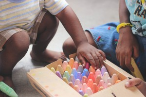 Hands of little children taking coloured chalks out of a box.  Anticipation: distasteful, or delicious?