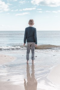 Little boy standing on the beach, looking out to sea.  Losing my child to school