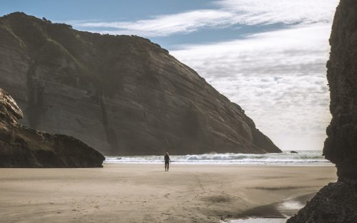 Figure walking alone on a beach with high cliffs either side. Waiting for the promised treasure
