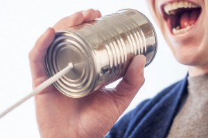 Man speaking into one half of a telephone made up of tin cans. Well, that was awkward