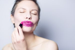 Woman smearing bright pink lipstick all around her lips. You can't go out wearing that...