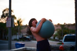 Boy holding a gym ball.  And this, too, shall pass