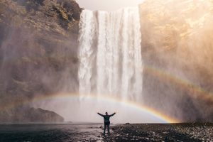 Man in front of a rainbow, which is in front of a waterfall. Is your life cupcakes and rainbows