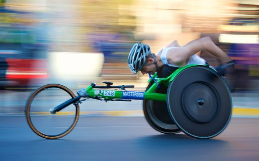 So you think you're normal? Man in a race in a 3-wheeled sports wheelchair with a fuzzy background, as if he is travelling at speed
