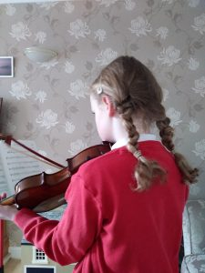 Girl with plaits playing the violin. Sibling rivalry: too hot to handle?