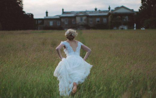 Bride running shoeless through a field. You can run but you can't hide