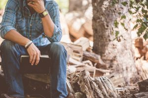 Man sitting thinking on a pile of firewood.  Well, that was awkward
