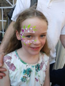 Smiling girl with flowers painted around her right eye. Just can't let go