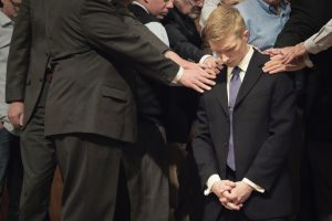 Blonde boy at a funeral. To live, or to live and let die?