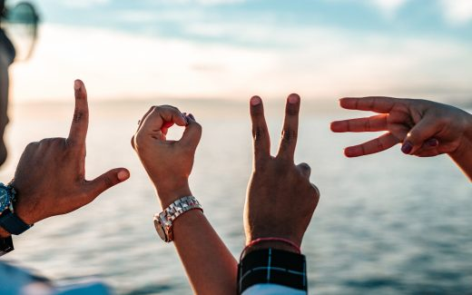 "Hands held up over the sea, spelling out the word ""love"". How many friends do you have?"