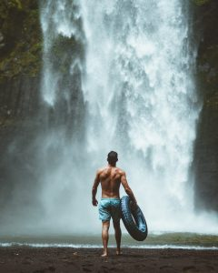 Man in front of a waterfall in swimming shorts, holding a rubber ring. Being rebellious, or going wild?