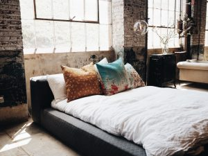 Low bed with white linen and colourful cushions.  What do you take to bed: 5 tips for a better night's sleep