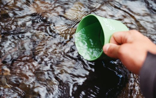 Getting water from a stream into a green cup. Surviving the school holidays