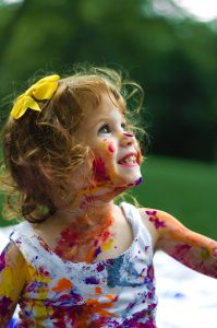 Smiling toddler with lots of paint on her neck, face and arms. How do you find joy?