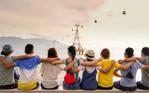 Group of teenagers with their arms around each other's shoulders sitting on a sea wall. Groups: are you in or are you out?