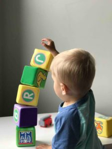 Little boy building a tower of wooden blocks.  What are you grafeful for?
