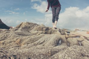 Woman walking in bare feet on rocks at the beach. Is attitude a self-fulfulling prophecy?