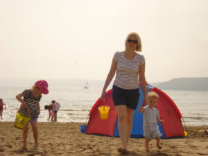 Mother and two small children on a beach.  Taking people as they are