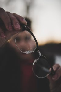 Pair of glasses being held by a man in soft focus.  Taking people as they are