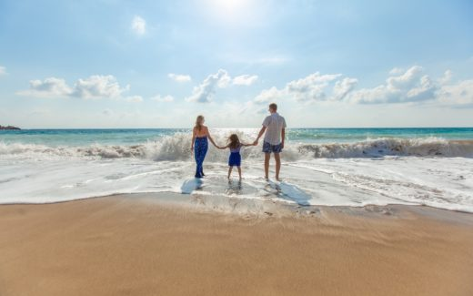 Mum, Dad and child in the edge of the surf on a sandy beach. How I sabotaged my holiday
