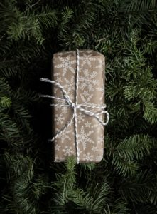 Present wrapped in gold paper with a pine tree behind. What presents did you get for Christmas?