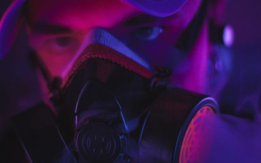 Person wearing a gas mask in purple lighting. Social distancing: a mental health guide