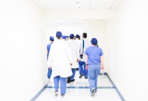 Doctor and nurses walking away from the camera down a white corridor. Lockdown: what have we learnt so far?