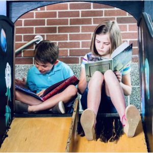 A girl and a boy reading at the top of a wooden slide. Working from home: coping during lockdown