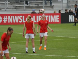 Girls in red and white kits playing football. How are your skills?